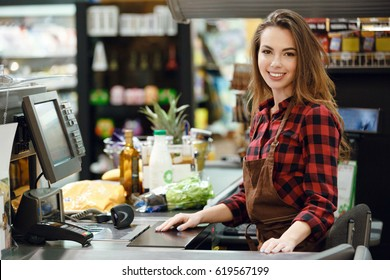 Image Of Cashier Lady On Workspace In Supermarket Shop Looking At Camera