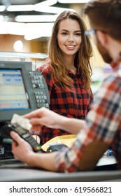 Image of cashier man on workspace in supermarket shop create payment with credit card. Focus on lady near cashier's desk.