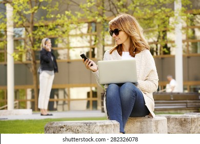 Image of casual businesswoman sitting at outdoor while using her laptop and making call with mobile. Business people at work.