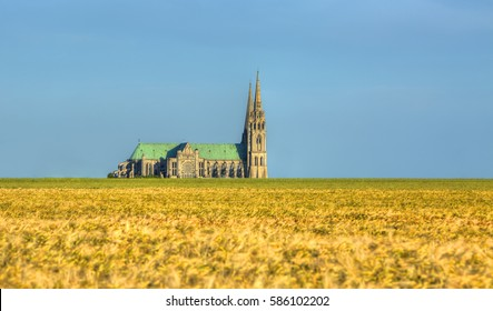 Image of the Cathedral of Our Lady of Chartres seen from outside of the city above the fields of cereals which surround the locality.