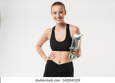 Image of caucasian joyful woman wearing tracksuit smiling and holding bottle of water isolated over white wall