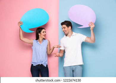 Image of caucasian man and woman holding copyspace banners for announcement isolated over colorful background