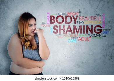 Image of Caucasian obese woman looks fearfully while standing with text of body shaming in the studio