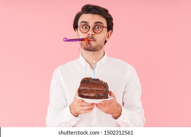Image of caucasian surprised man wearing eyeglasses holding chocolate cake with candle isolated over pink background