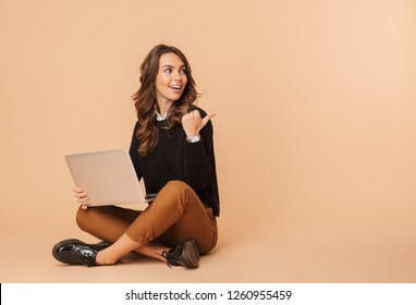 Image of caucasian woman 20s using laptop while sitting on floor isolated over beige background