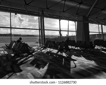 The image of chairs at the airport for passengers and have two men are sitting on chair, this image was process black and white style and like silhouette photo.