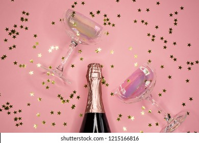 image of champagne coupes and bottle on pink background