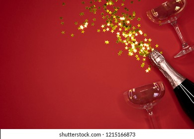 image of champagne coupes and bottle on red background