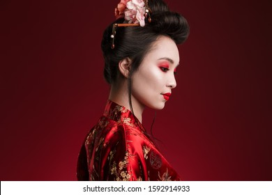 Image of charming geisha woman in traditional japanese kimono looking downward isolated over red background