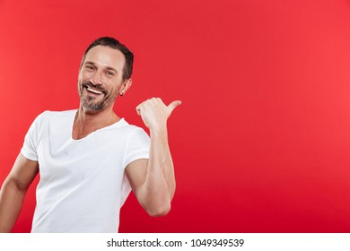 Image of cheerful adult man standing isolated over red background looking camera pointing.