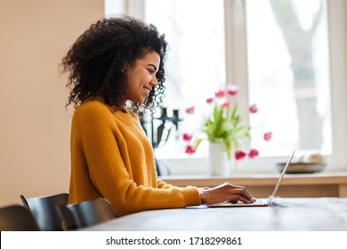 Image of cheerful african american woman using laptop while sitting at table in living room