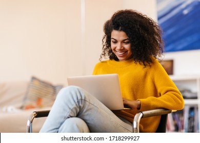 Image of cheerful african american woman using laptop while sitting on chair in living room