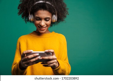 Image of a cheerful african curly woman posing isolated over dark blue wall background listening music with headphones play games by smartphone.