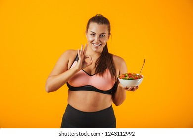 Image of cheerful chubby woman in tracksuit holding plate with green salad isolated over yellow background