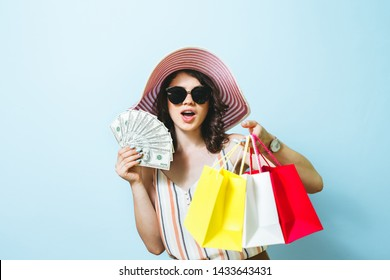 Image of cheerful elegant young woman in sunglasses holding fan of money and colorful shopping bags, isolated over blue background