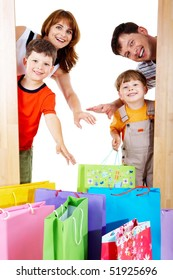 Image of cheerful family members near colorful shopping bags looking with happy expression