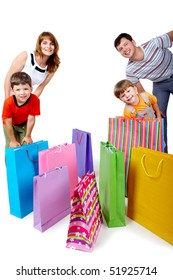 Image of cheerful family members near colorful shopping bags looking at camera