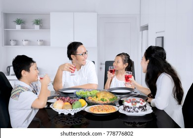 Image of Cheerful family talking each other while having lunch in the kitchen