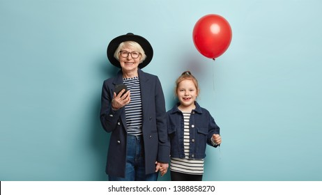 Image of cheerful grey haired woman in hat, holds mobile phone, sends text message, keeps hand of little granddaughter who carries red balloon, isolated over blue background. Family and celebration