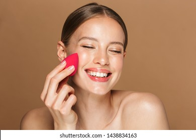 Image of a cheerful happy young amazing woman posing isolated over brown chocolate background wall holding makeup sponge.