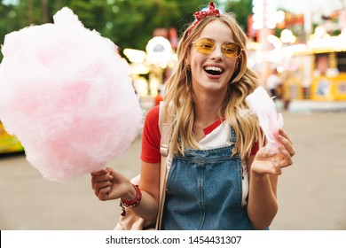 Image of a cheerful laughing young blonde woman in amusement park holding cotton candy candyfloss.