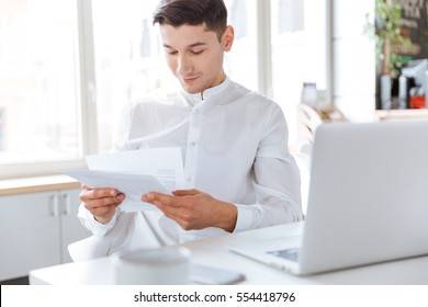 Image of cheerful man dressed in white shirt holding documents while using laptop computer. Coworking. Looking at documents.