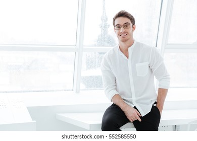 Image of cheerful man wearing eyeglasses and dressed in white shirt sitting on white table. Looking at camera.
