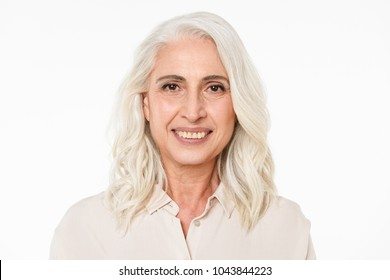 Image of cheerful mature old woman standing isolated over white background wall looking camera.