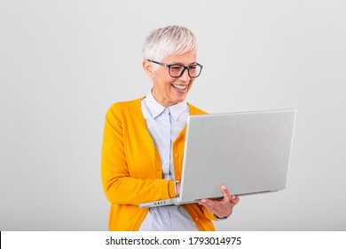 Image of cheerful mature woman standing isolated over gray background using laptop computer. Portrait of a smiling senior lady holding laptop computer