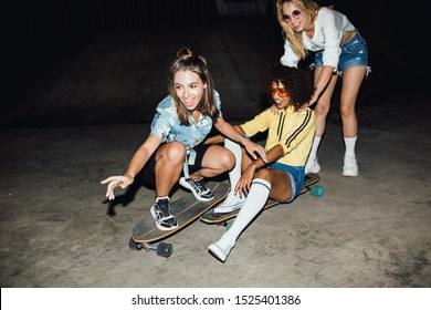 Image of cheerful multiethnic girls in streetwear smiling and riding skateboards at night outdoors
