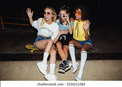 Image of cheerful multinational girls in streetwear smiling and sitting on skateboards at night party outdoors