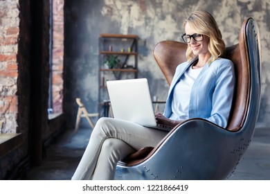 Image of cheerful office woman with blond hair in business wear sitting on chair and working with laptop office