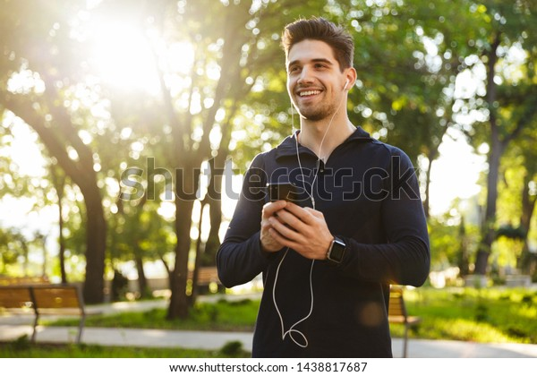 Image of a cheerful optimistic young sports fitness man standing in green park nature using mobile phone chatting listening music.