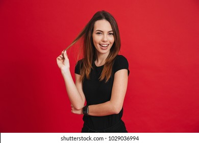 Image of cheerful pretty woman with long brown hair smiling on camera and touching strand with playful or flirting view, isolated over red background