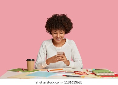 Image of cheerful young African American writer being inspired by good message recieved on mobile phone, writes poetry in personal organizing notebook, uses modern cell phone during coffee break