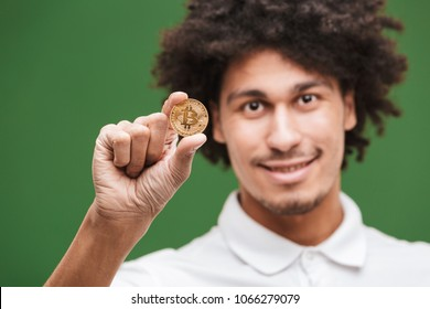 Image of cheerful young african curly man isolated over green wall background holding bitcoin.