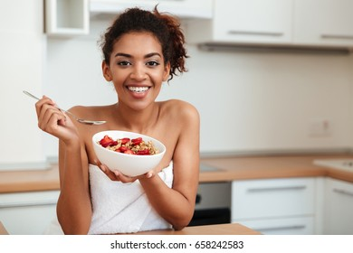 Image of cheerful young african woman dressed in towel sitting at home and looking at camera while eating strawberry with muesli.