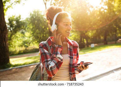 Image of cheerful young african woman walking outdoors in park. Looking aside listening music while chatting by phone.