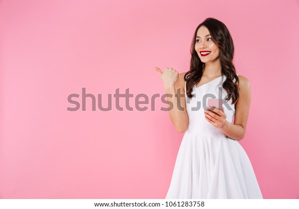 Image of cheerful young asian woman standing isolated over pink wall background looking aside pointing using mobile phone.