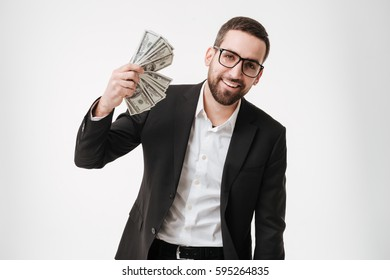 Image of cheerful young bearded businessman wearing eyeglasses over white background holding money in hands.