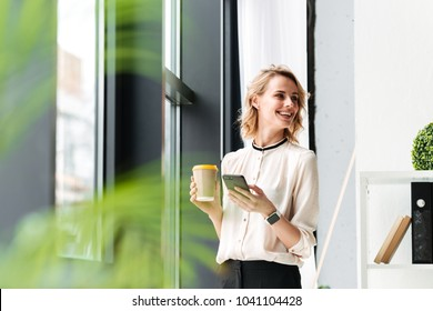 Image of cheerful young business woman in office looking aside chatting by mobile phone drinking coffee.