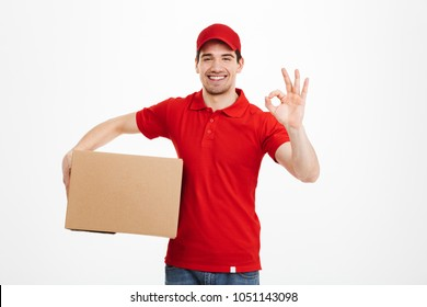 Image of a cheerful young delivery man in red cap standing with parcel post box isolated over white background showing okay gesture.