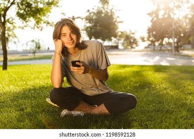 Image of cheerful young guy sitting on grass in the park chatting by phone.