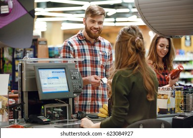 Image of cheerful young man standing in supermarket shop near cashier's desk holding credit card. Looking aside.