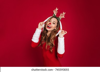 Image of cheerful young woman wearing christmas deer costume standing isolated over burgundy background wall. Looking at camera.