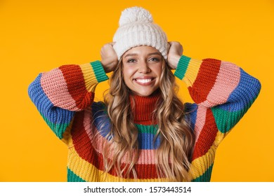 Image of cheerful young woman in winter hat and sweater smiling at camera isolated over yellow background