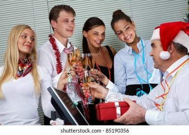 Image of cheering associates congratulating ceo in Santa cap at corporate party