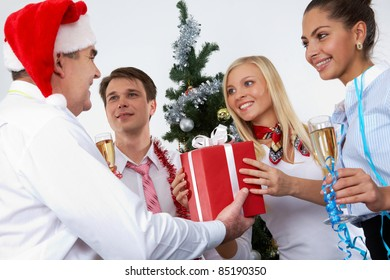 Image of cheering associates taking gifts from ceo in Santa cap at corporate party