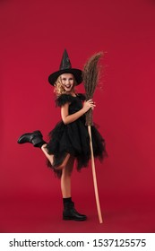 Image of cheery little girl witch in carnival halloween costume isolated over red wall background with broom.