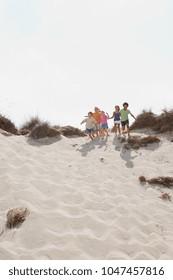 An image of Children running down a dune